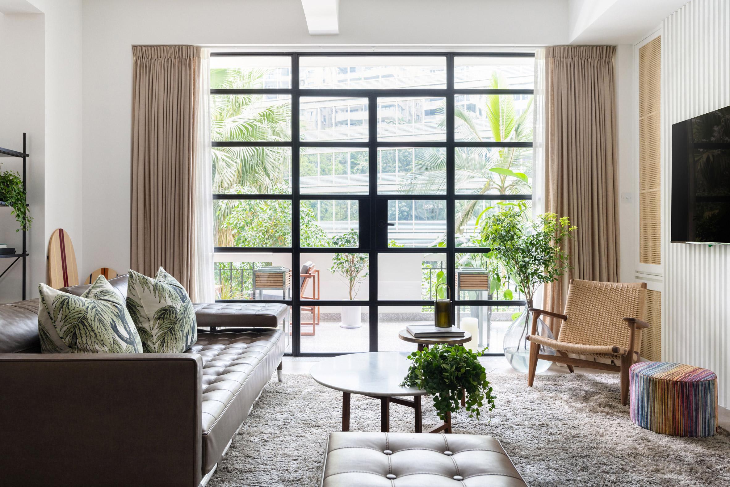 Living room with steel balcony doorway in Grosvenor Residence by Lim + Lu