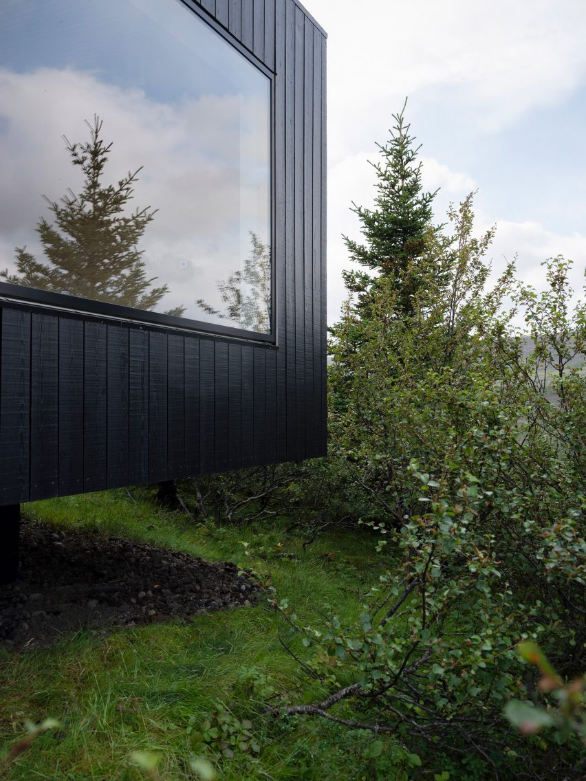 A facade with a large window and blackened-wood cladding