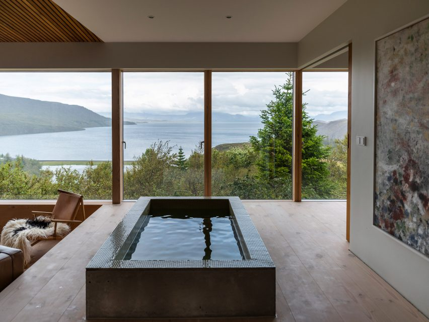 A pared-back lounge with a bathtub overlooking Lake Thingvallavatn