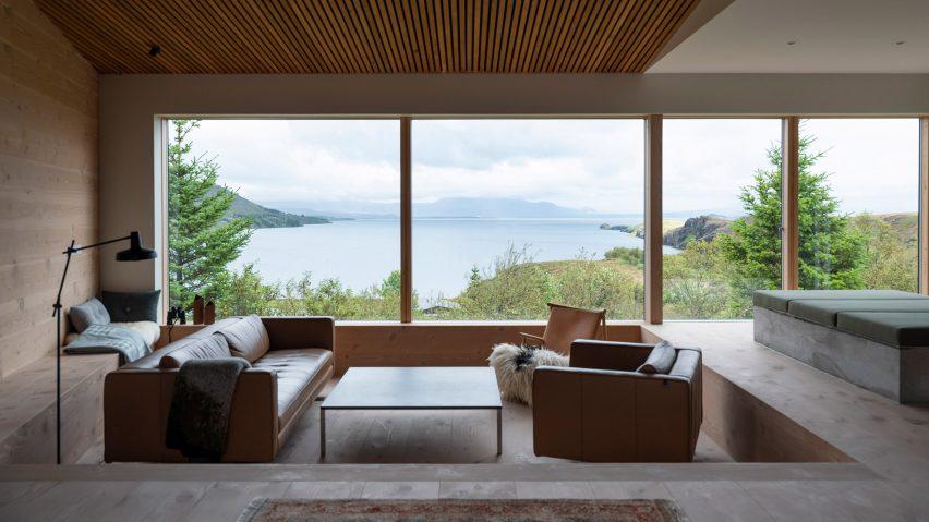 A sunken lounge with large windows framing a lake