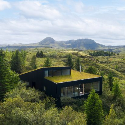 A black house with a green roof in rural Iceland
