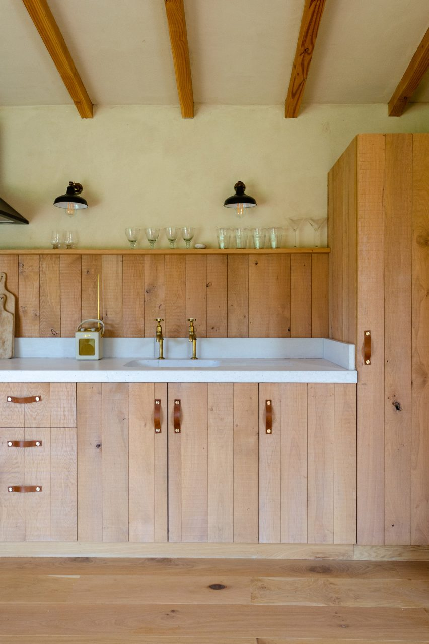 A cabin's wooden kitchen with leather handles