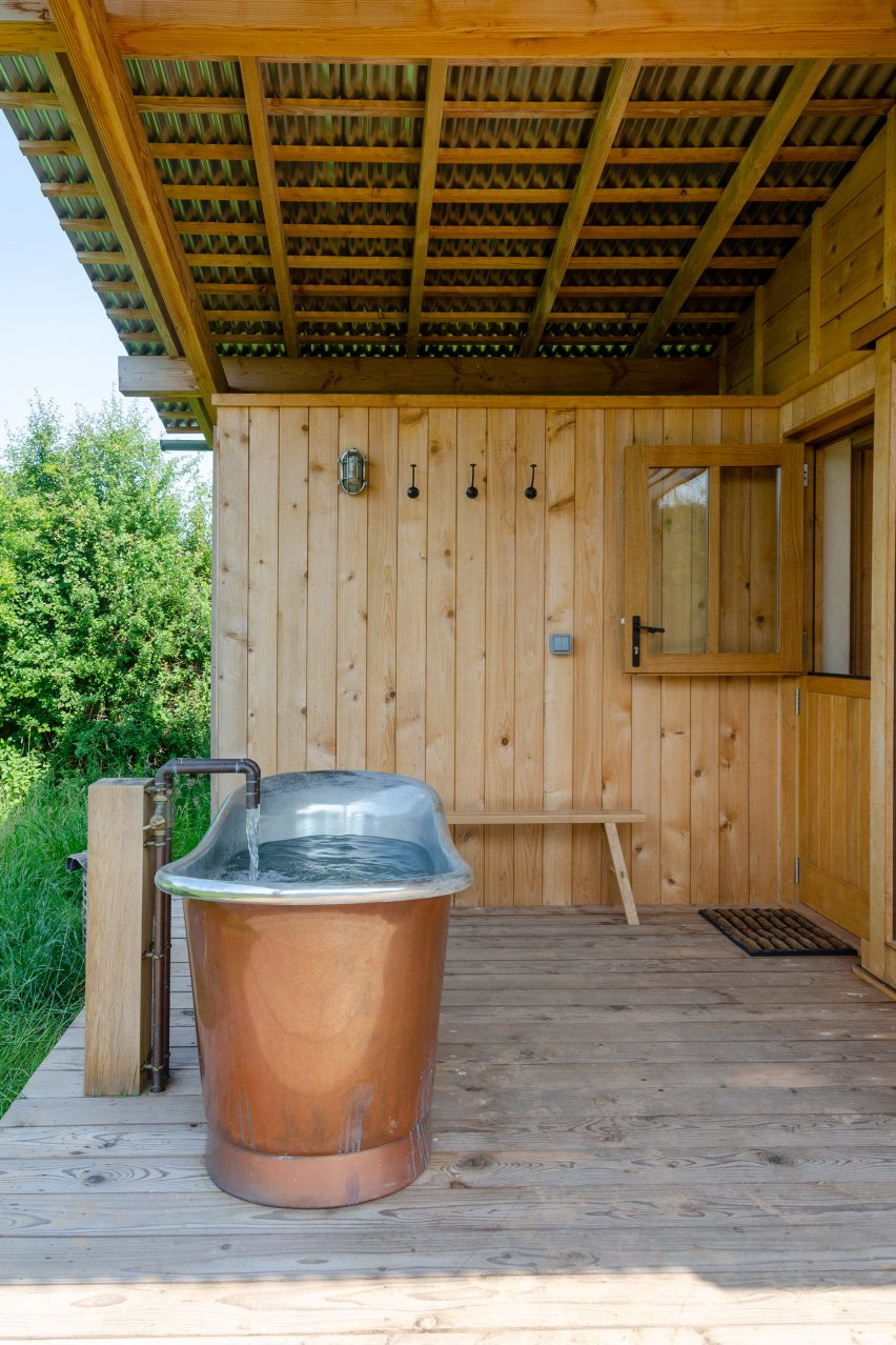 A cabin terrace with a freestanding copper bathtub