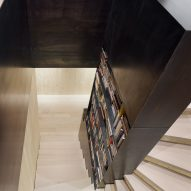 A spruce staircase with a black-steel bookcase