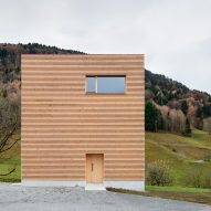 The minimalist timber-clad facade of an Alpine house