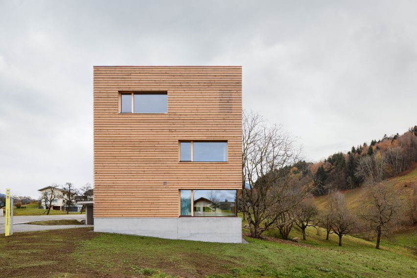A square timber-clad house with a concrete base