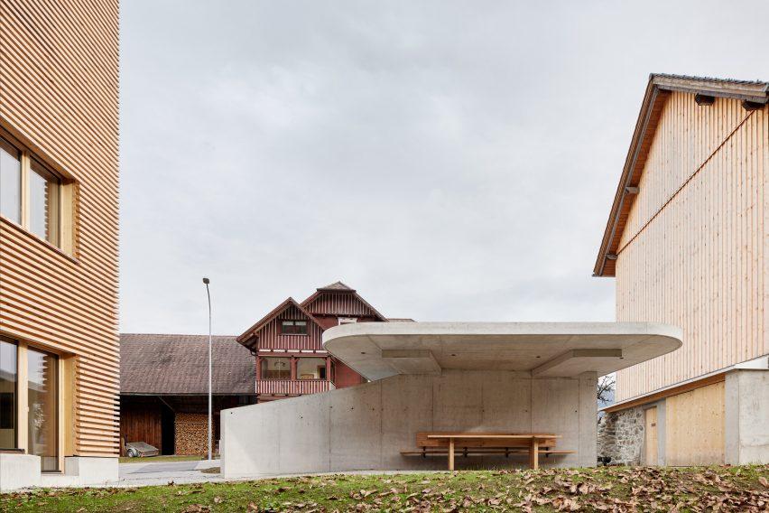 A concrete carport outside a timber-clad house