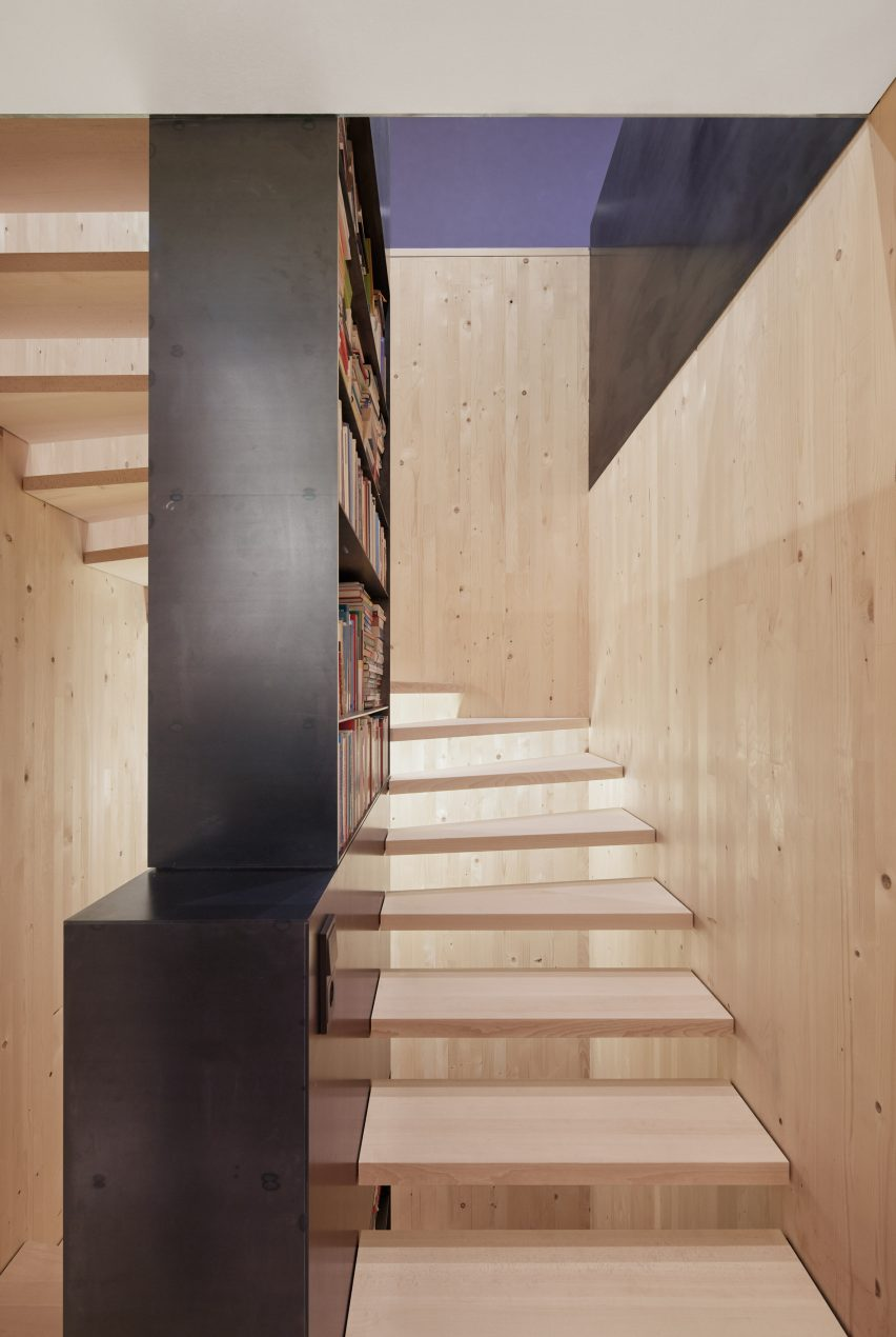 A spruce open-tread staircase with a black steel bookcase