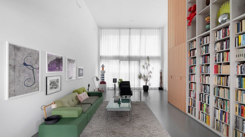 Living room and double-height storage walls in Home of the Arts by i29