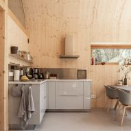 Grey kitchen units against wood-lined walls