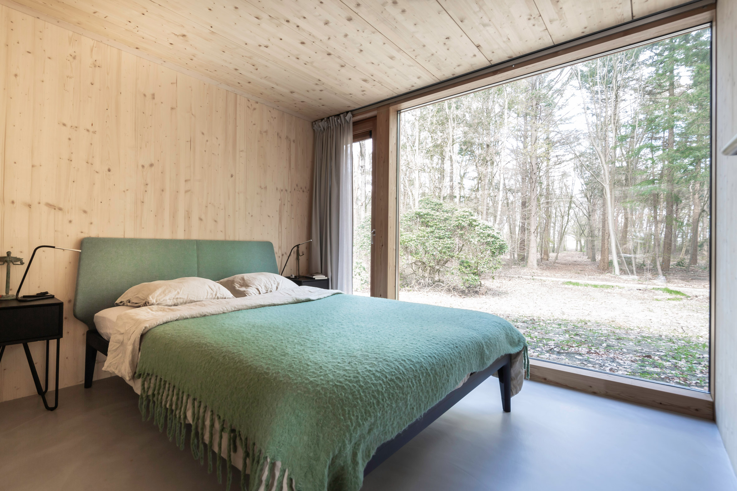 A bedroom with a floor-to-ceiling window