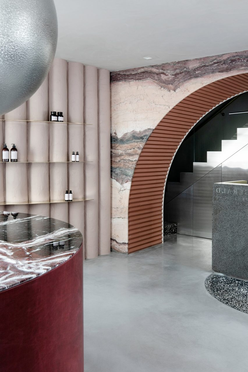 Marble accents and undulating plaster wall in skincare clinic