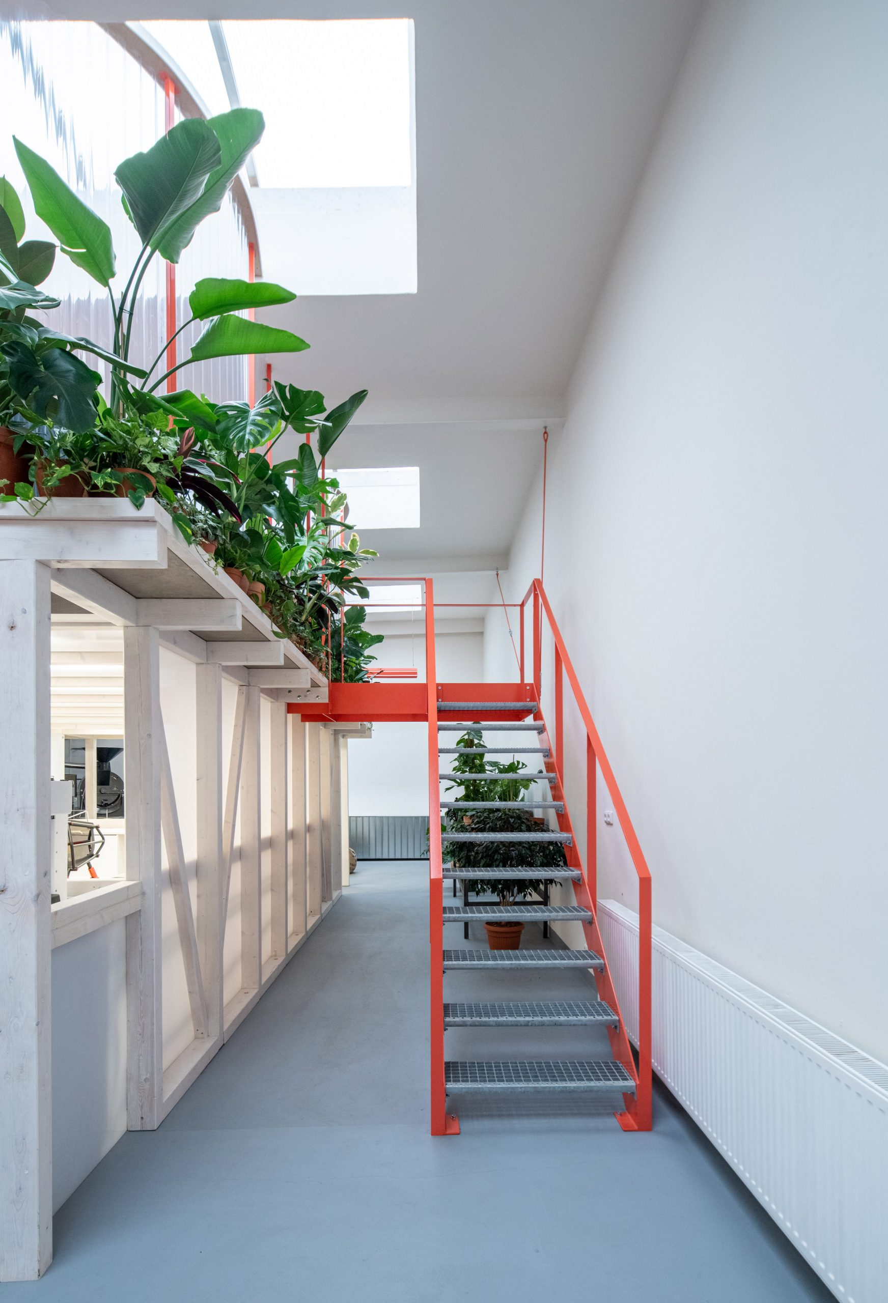 Tangerine-coloured stairs leading up to mezzanine in cafe by Kogaa
