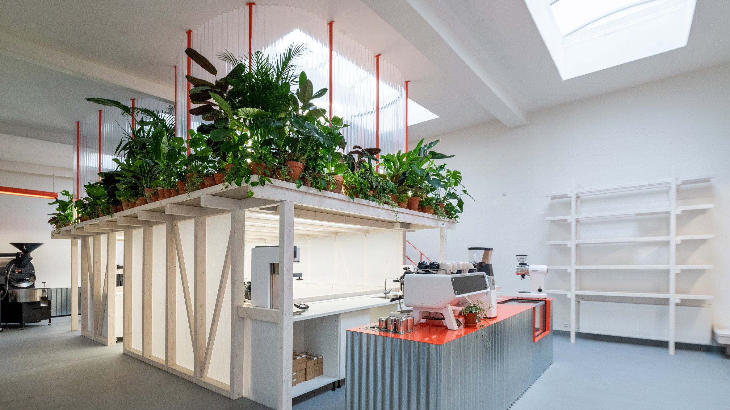 Plant-fringed mezzanine and corrugated metal counter of Grounds Coffee Hub