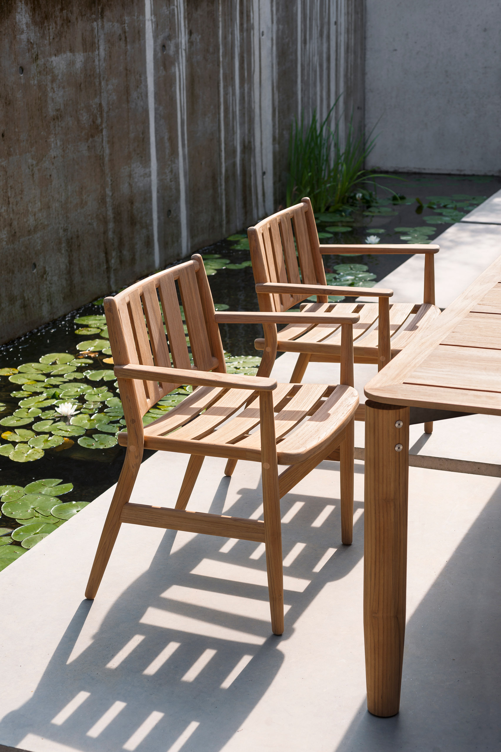 A pair of outdoor dining chairs made from teak