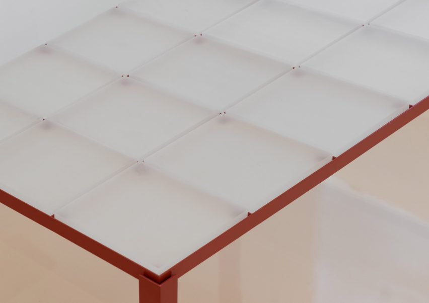 Red steel table inlaid with square resin tiles from store interior by Say Architects