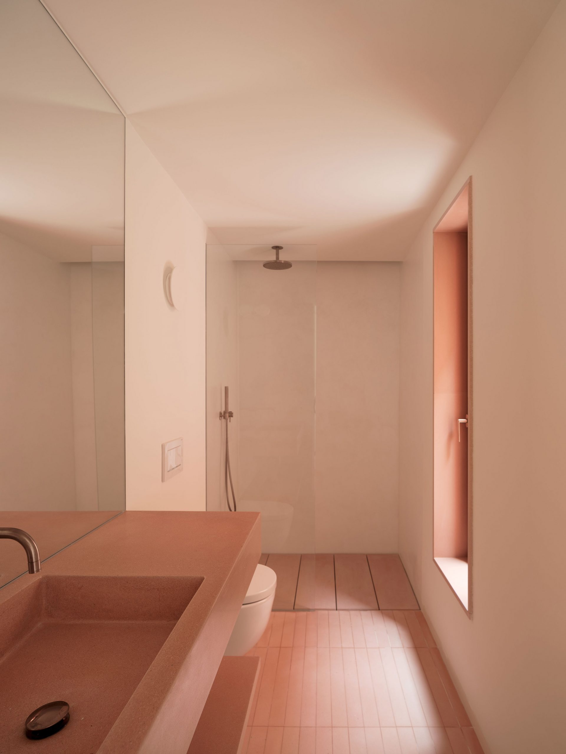 A pink-hued bathroom with a concrete sink