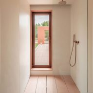 A white-walled shower with a pink concrete floor