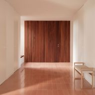 A holiday home entrance area with a pivoting wooden door