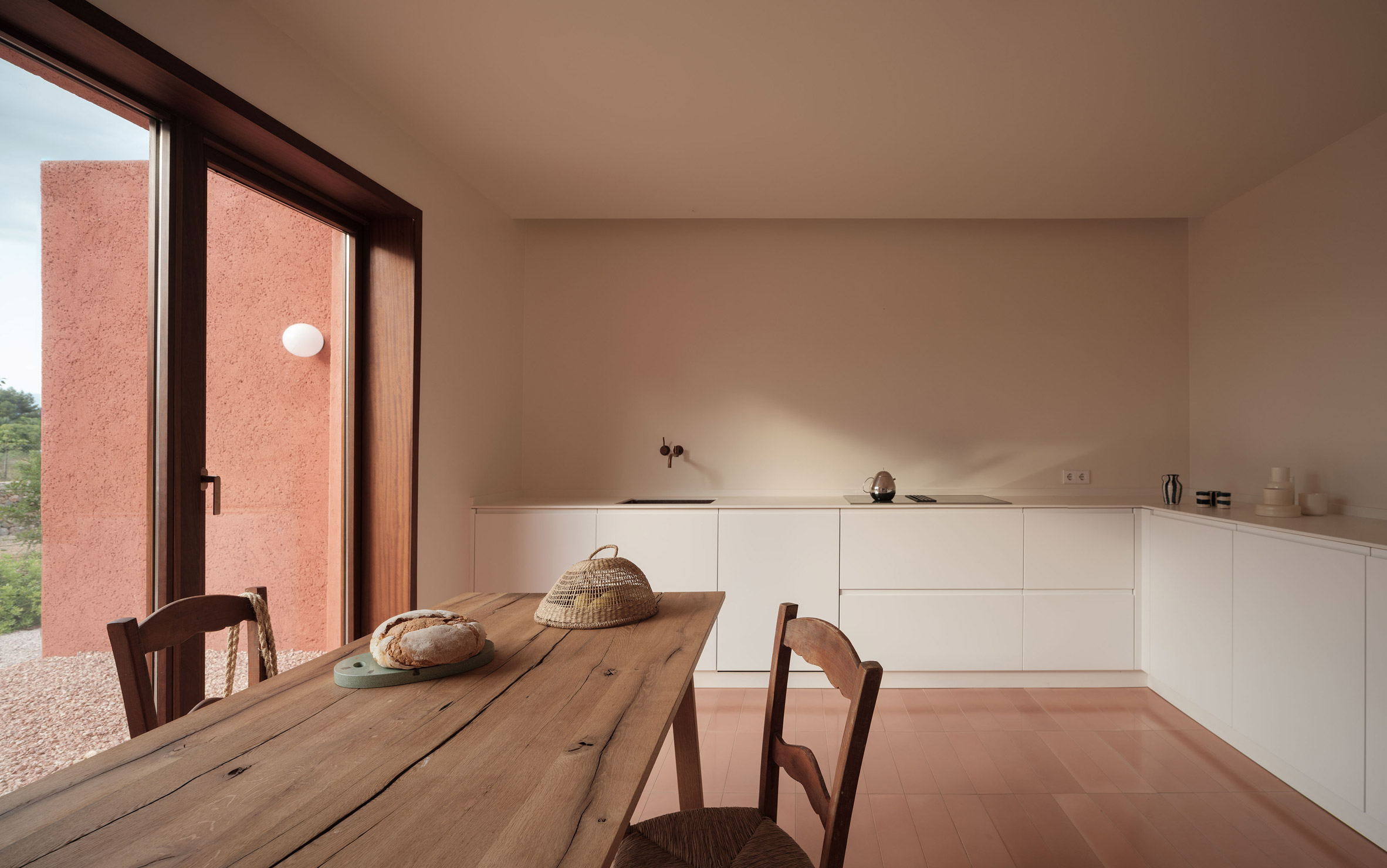A pared-back kitchen with a wooden table and pink floor tiles