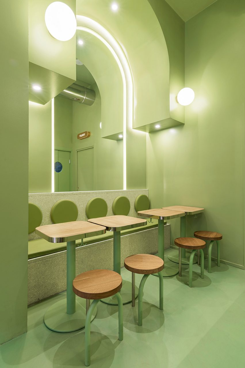Green seating area with arched ceiling and wooden accents in Milan burger joint