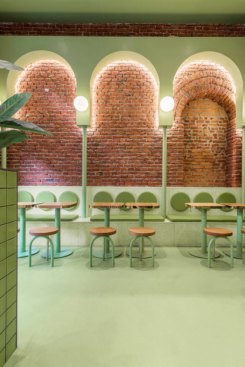 Green arches and exposed brick in seating area of Bun restaurant by Masquespacio
