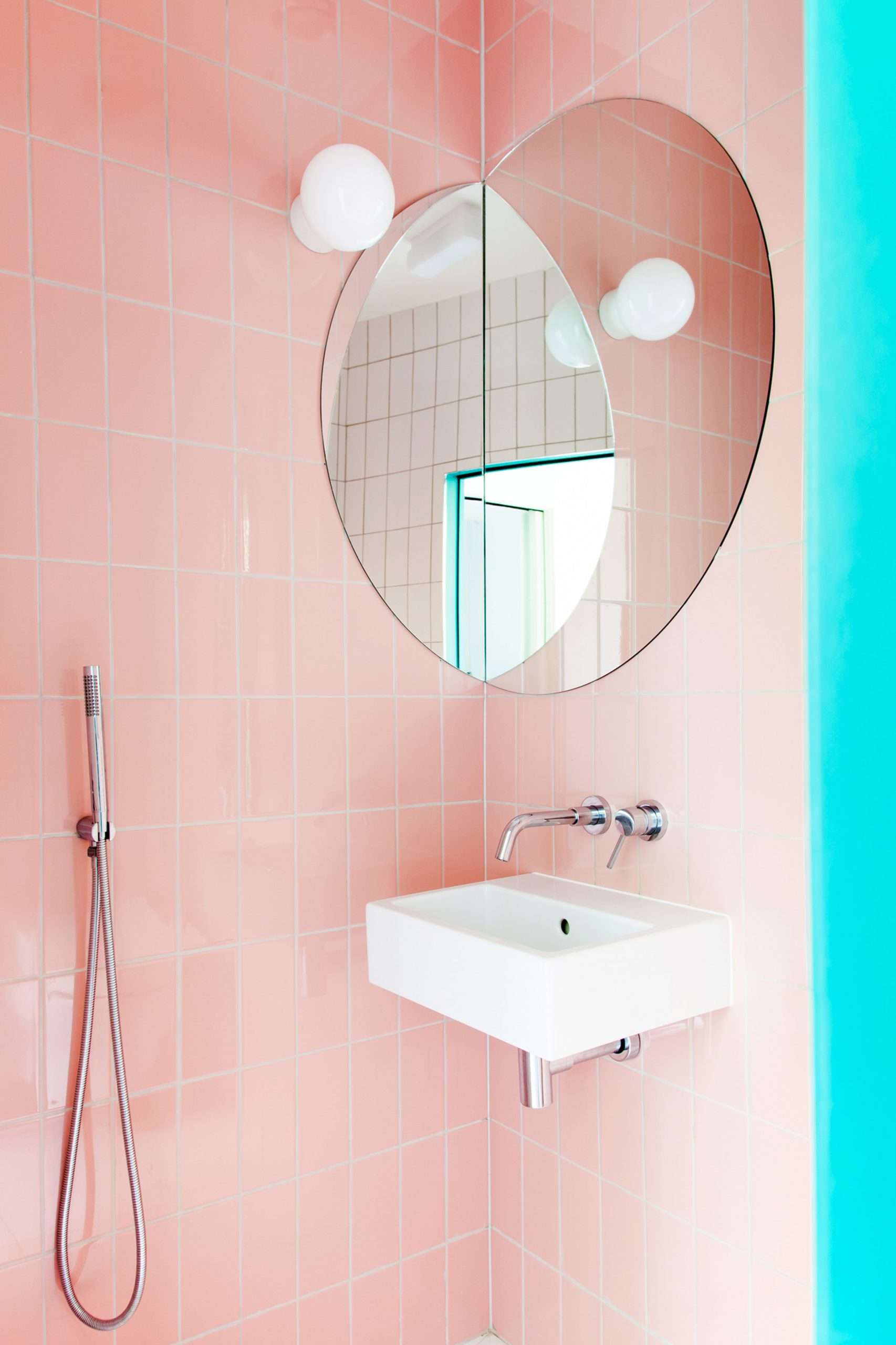 A bathroom with pink wall tiles