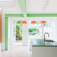 A bright white kitchen with green structural beams