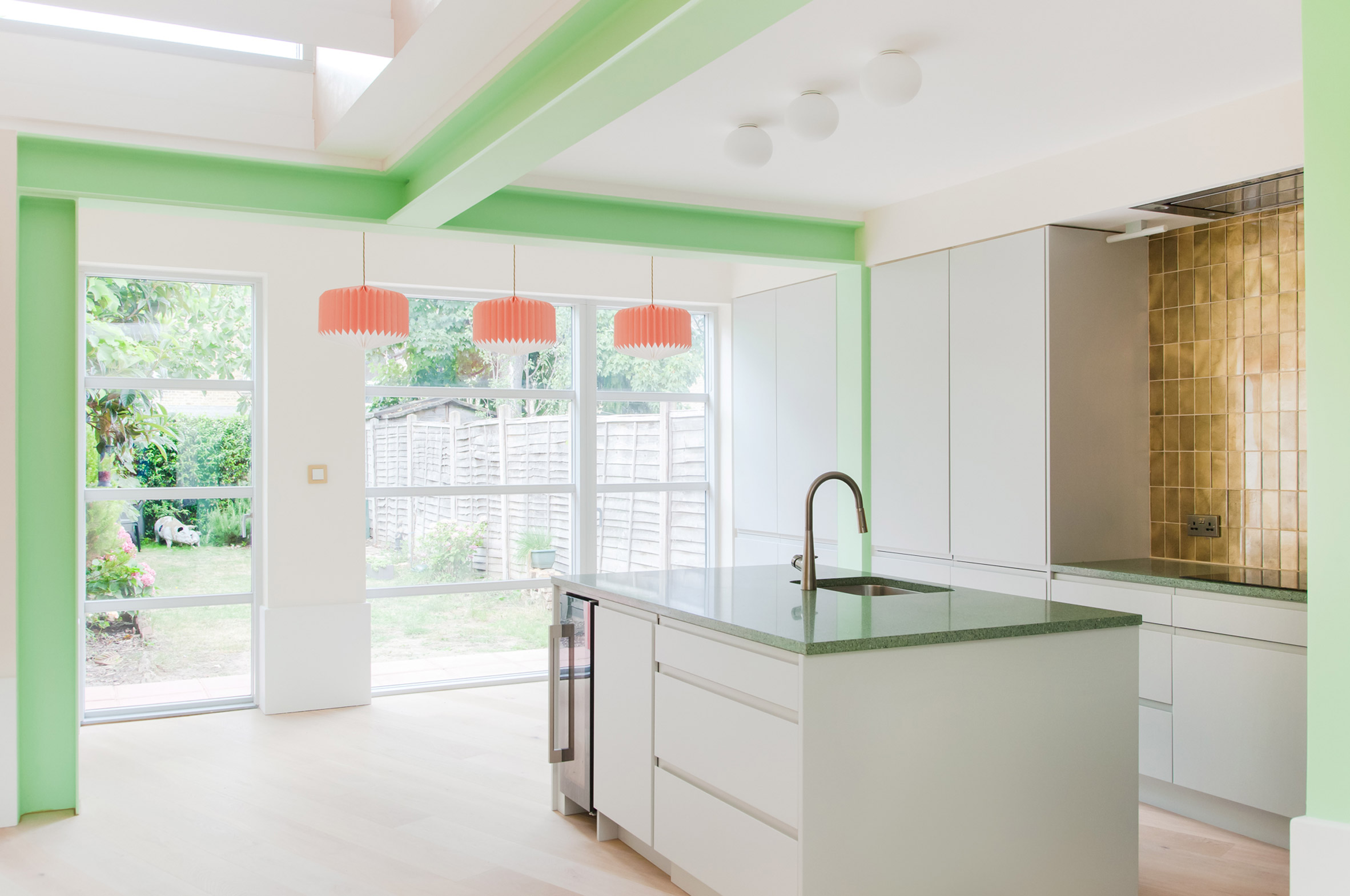 A white-walled kitchen with green-painted structural beams