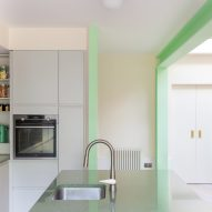 A white kitchen with green structural beams