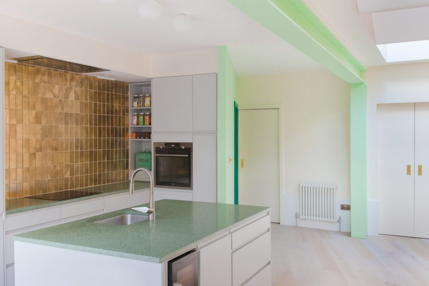 A bright white kitchen with green and gold detailing