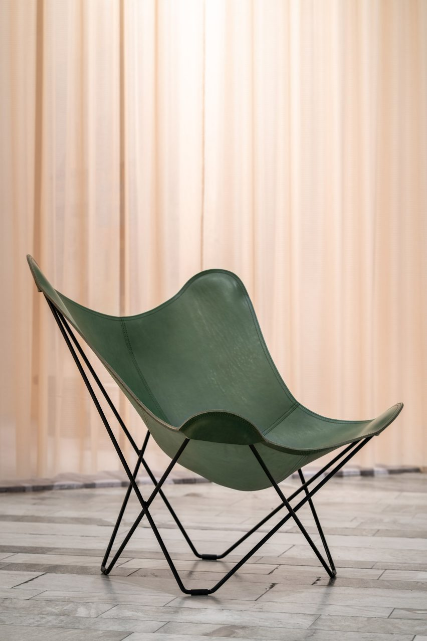 A green leather butterfly chair with a black frame