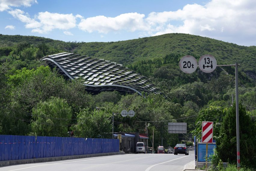 A curved shelter made from overlapping metal panels