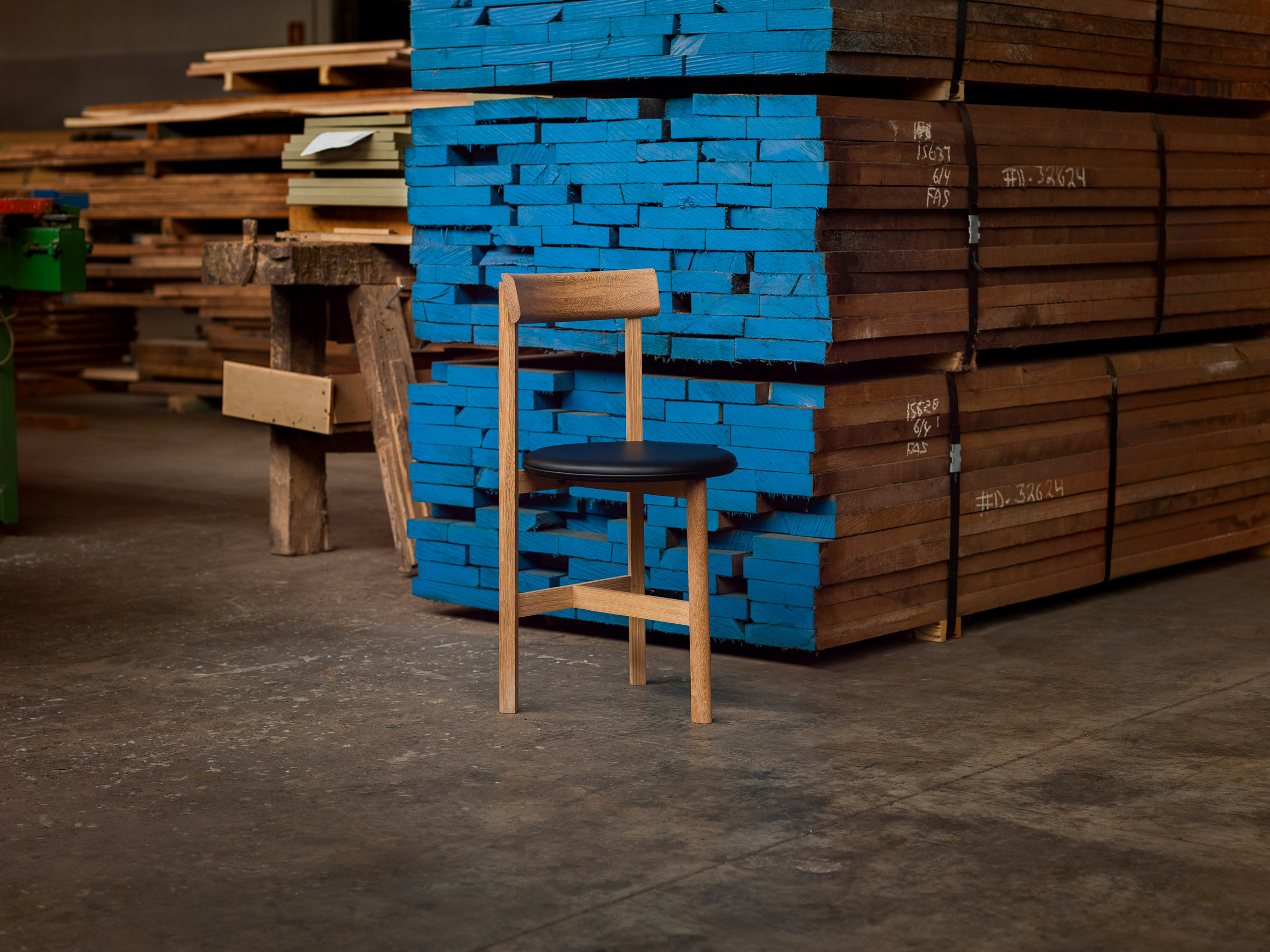It has a leather seat and a wooden frame by Neri&Hu