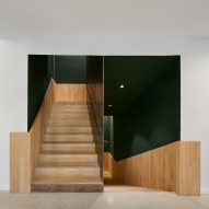 Wooden staircase fills the centre of the space