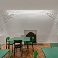 Green tables fill the historic manor