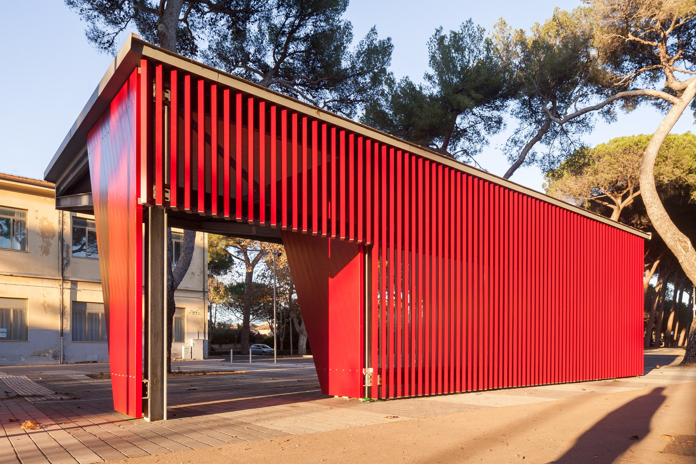 A red bus stop made from aluminium slats