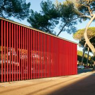 A slatted red bus stop