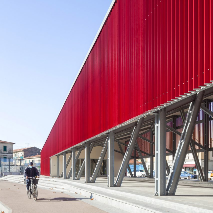 A cyclist beside a red pavilion