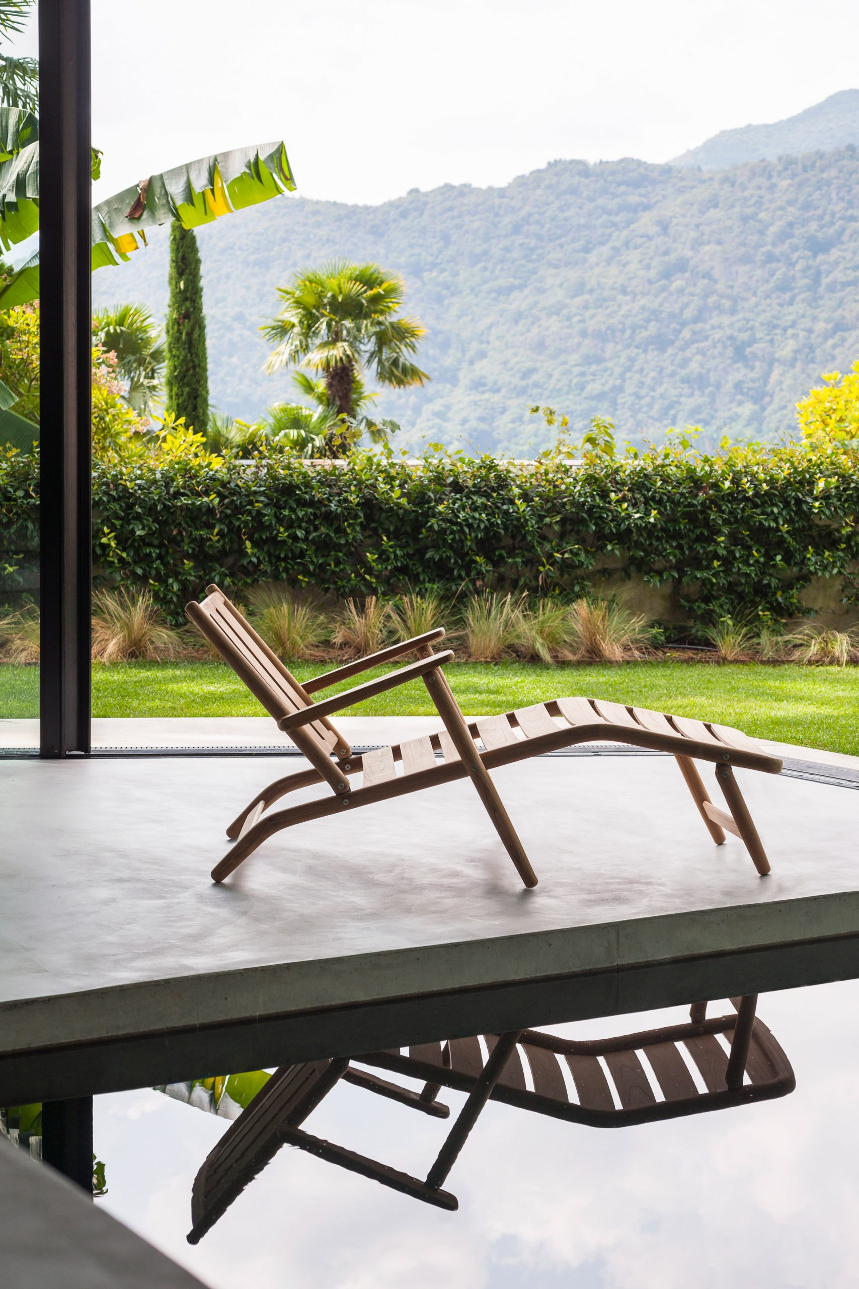 Teak wood chaise-longue by Roda in front of a pool
