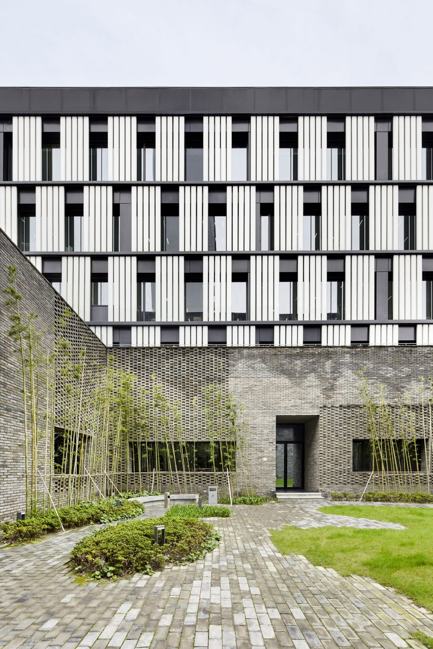 A monochrome office block with a grey brick base