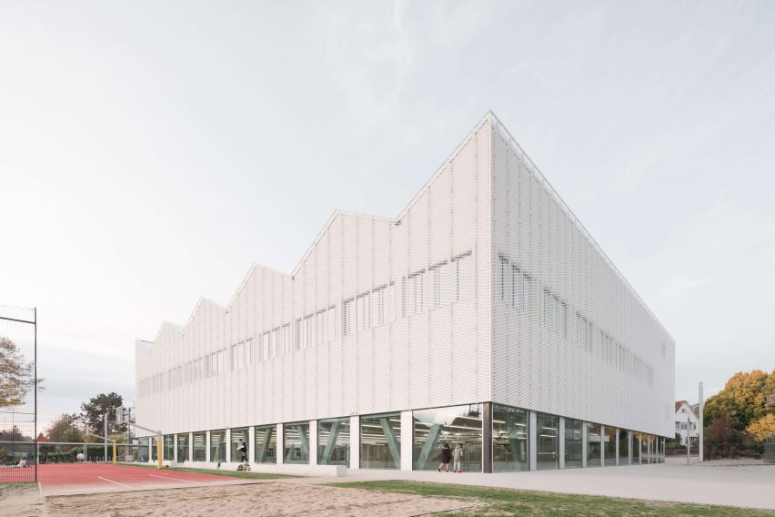 Glazed ground level exposes trusses by Wulf Architekten