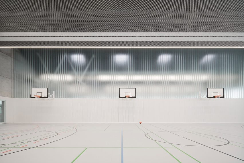 Basketball hoops are organised against a partially glazed wall