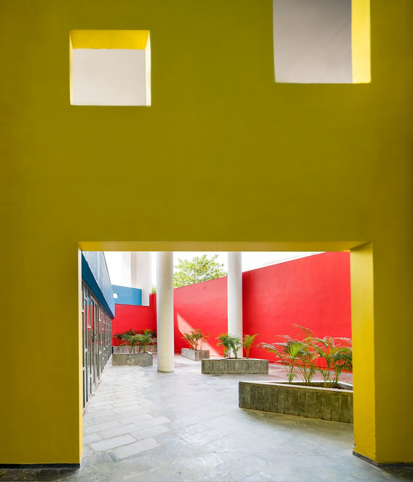 A courtyard lined with walls painted in primary colours