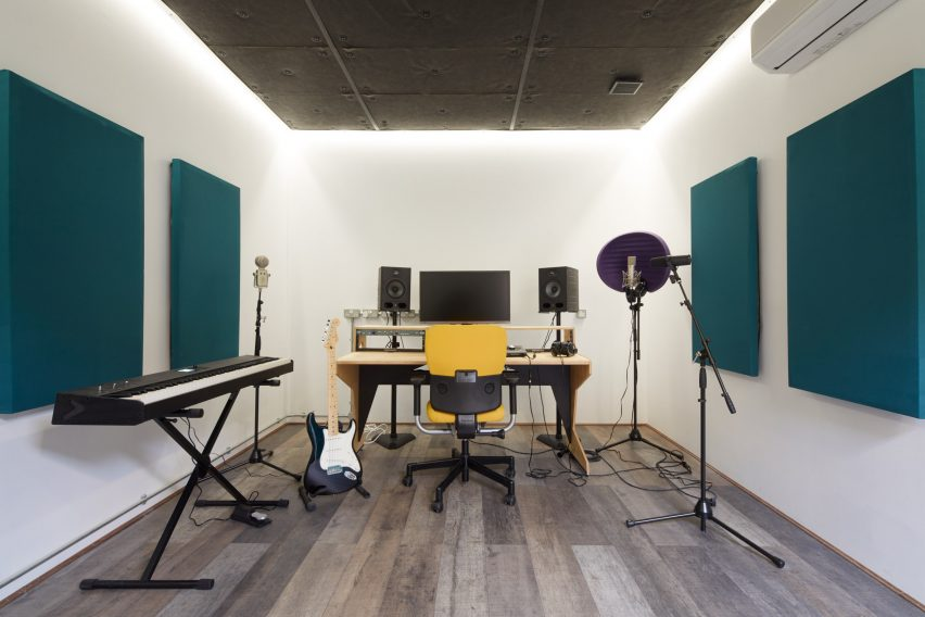 A white-walled music studio with teal acoustic panels