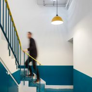 A teal-hued staircase with a yellow banister