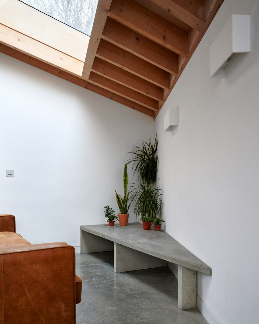 A white-walled living space with a timber ceiling