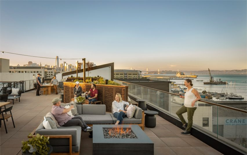 Rooftop terrace with fire pits by Woods Bagot