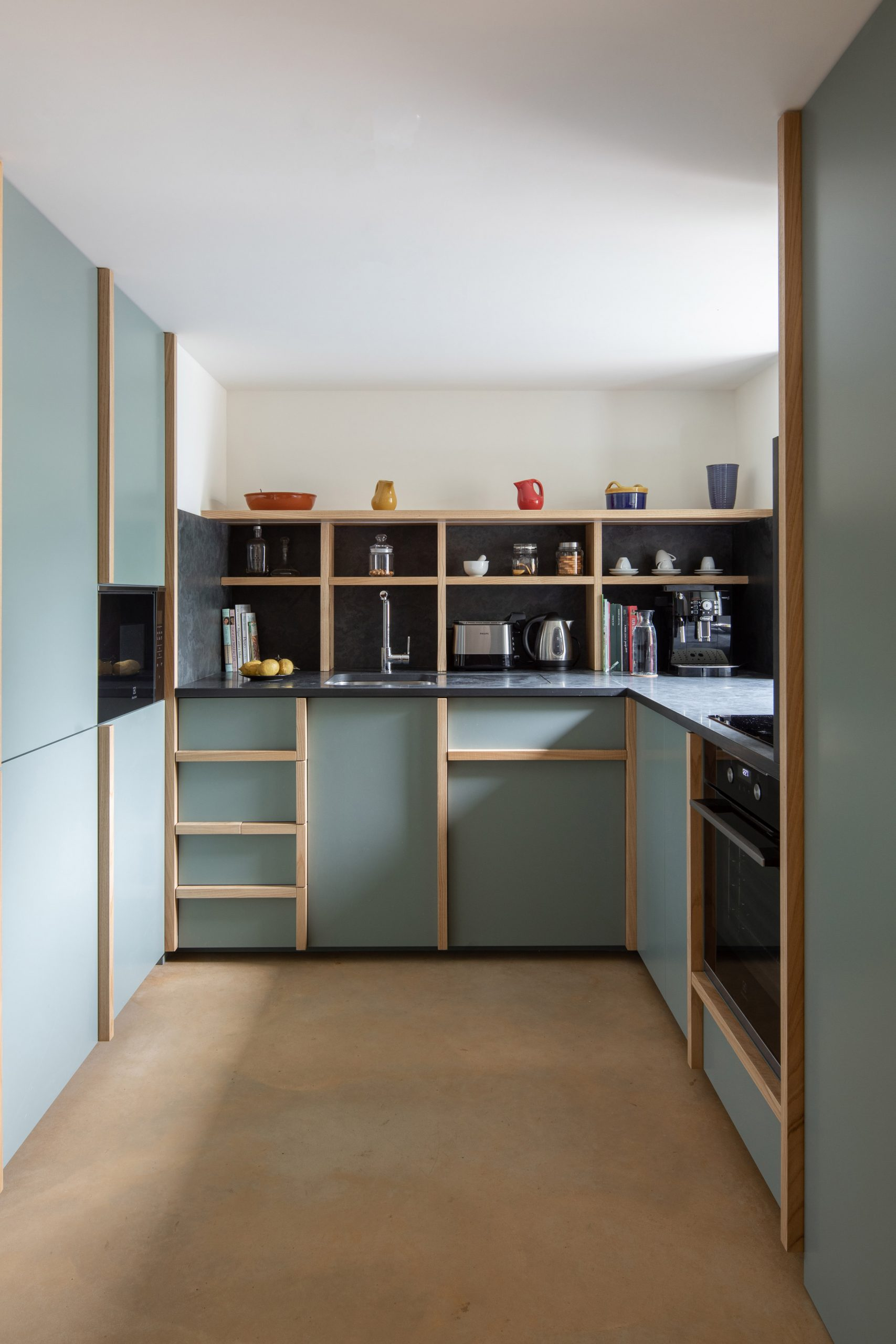 The kitchen is finished with a sage green by depA Architects