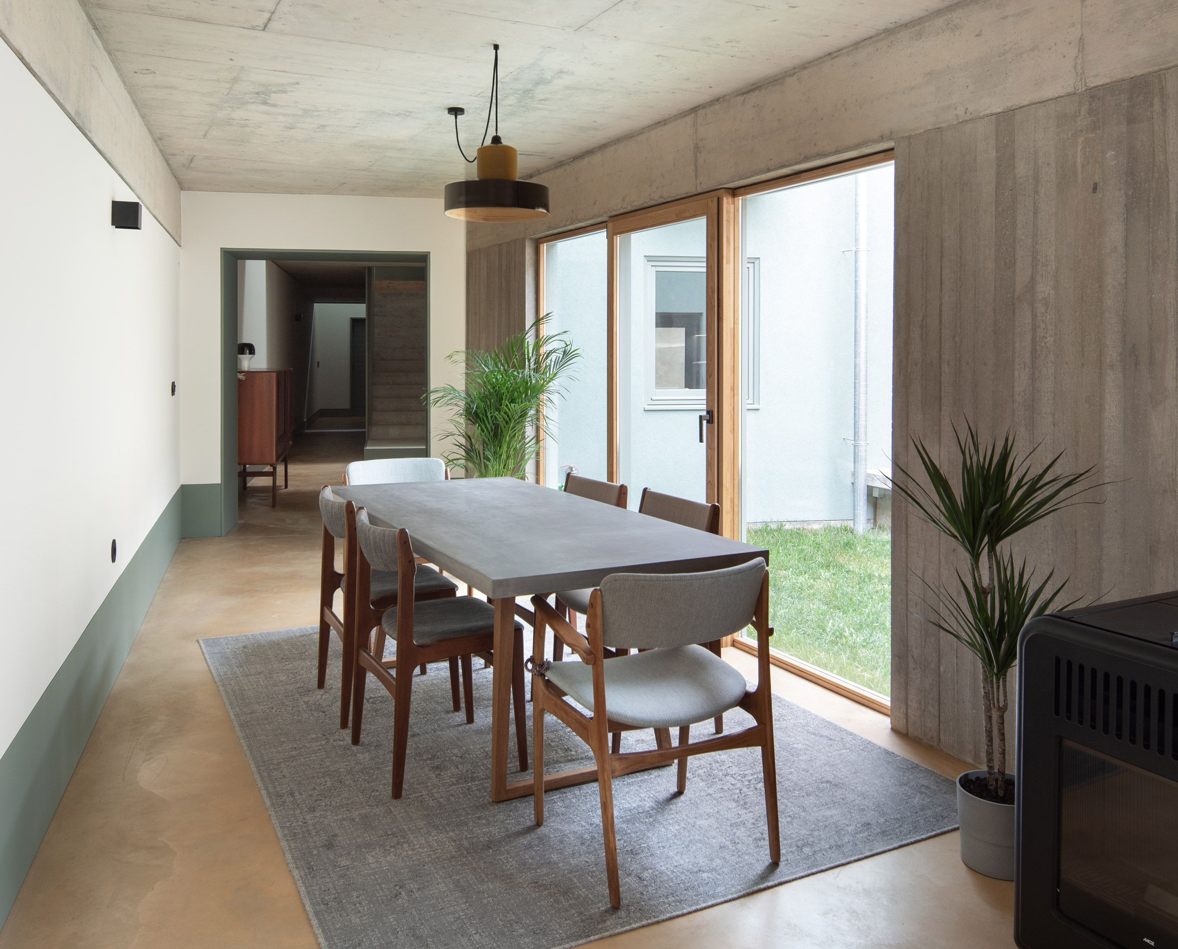 The dining area has board formed concrete walls by depA Architects